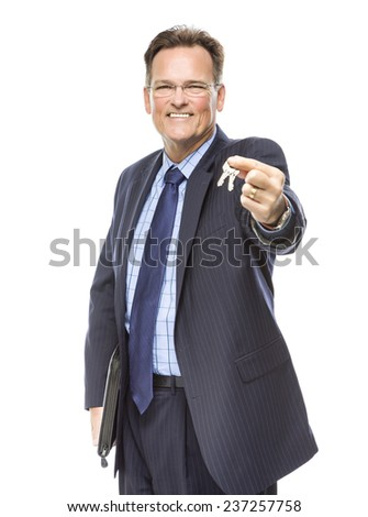 Handsome Real Estate Agent Holding Out Keys to New Home Isolated on a White Background. - stock photo