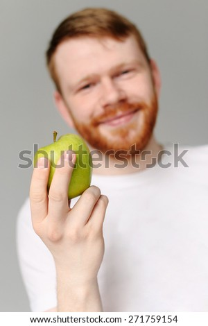 handsome red hair man with red beard in white shirt with green apple. Focus on the apple.