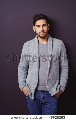 Handsome relaxed bearded young man in a stylish sweater and jeans standing leaning against a dark background with his hands in his pockets