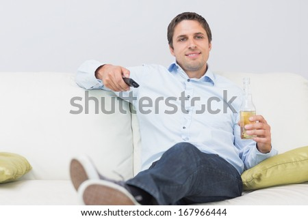 Handsome relaxed young man with a drink and remote control sitting on sofa in the living room at home - stock photo