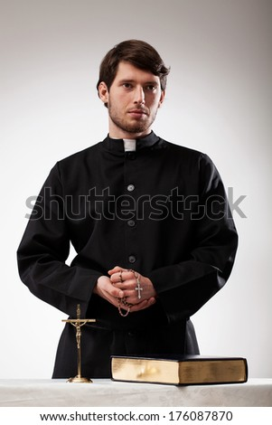 Handsome reverend with crucifix, rosary and the Bible - stock photo