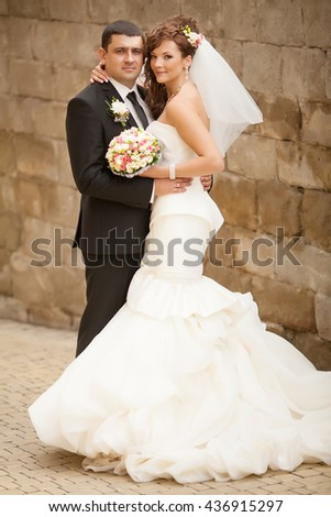 Handsome romantic groom kissing beautiful brunette bride near old wall castle