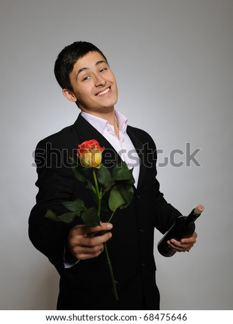 Handsome romantic young man holding rose flower and vine bottle  prepared for a valentines day. gray background