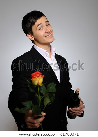 Handsome romantic young man holding rose flower prepared for a date. gray background