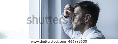Handsome sad businessman with personal problems standing in front of the window, panorama