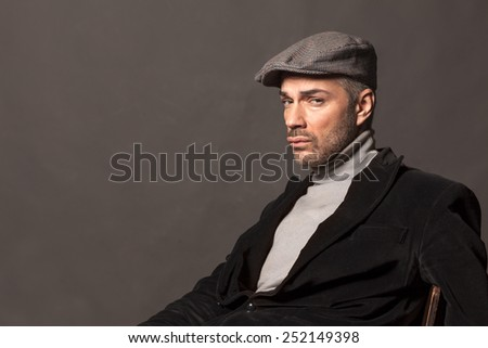 handsome sad man in jacket and cap in vintage style