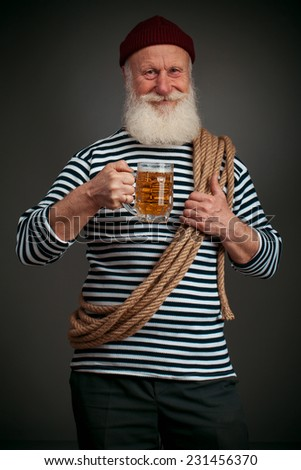 Handsome sailor isolated on black background. Seaman with beer - stock photo