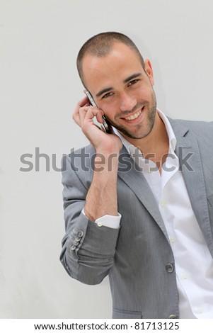 Handsome salesman talking on mobile phone - stock photo
