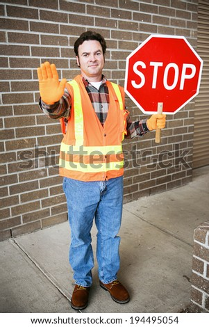 Handsome school crossing guard holding a stop sign.   - stock photo