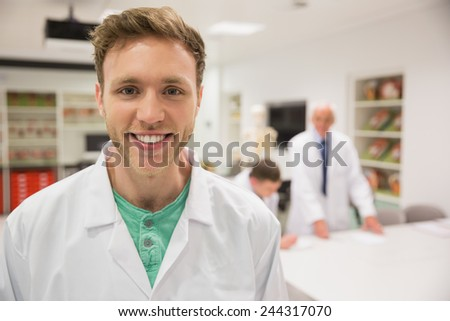 Handsome science student smiling at camera at the university - stock photo