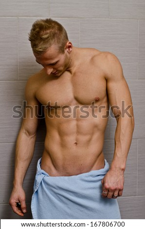 Handsome semi-naked muscular young man in bathroom with towel looking at his torso