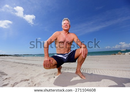 Handsome senior male in a squatting pose on the beach - stock photo