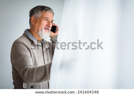 Handsome senior man calling on his cell phone and looking from a window at his house (shallow DOF; color toned image) - stock photo