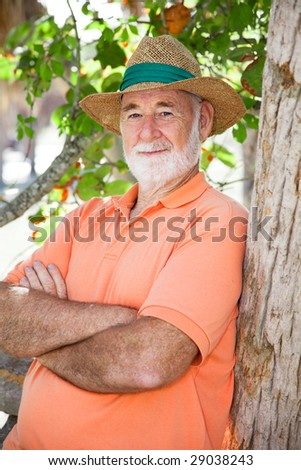 Handsome senior man in a panama hat with a wise, serious expression. - stock photo