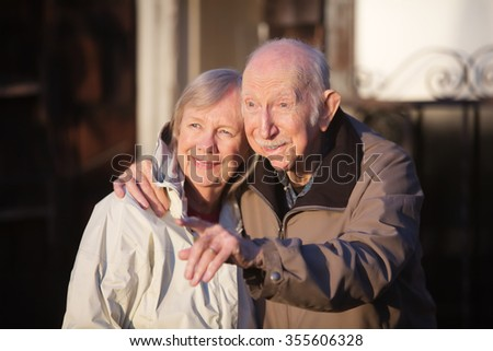 Handsome senior man pointing at something with his girlfriend - stock photo