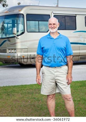 Handsome senior man posing in front of his luxury RV. - stock photo