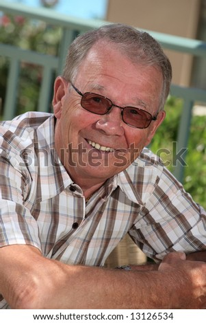 handsome senior man smiling relaxing outdoors