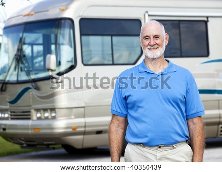 Handsome senior man standing in front of his luxury motor home. - stock photo