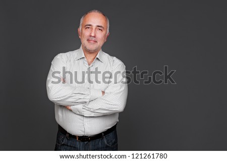handsome senior man with folded hands looking at camera and smiling. studio shot over grey background - stock photo