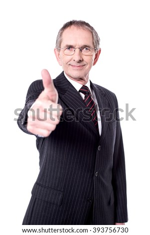 Handsome senior manager gesturing thumbs up over white