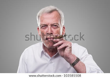 Handsome senior smoking a cigar. Handsome senior man with a shrewd expression and strong personaity smoking a cigar isolated on a grey studio background - stock photo