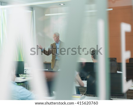 Handsome senior teacher and students group in computer lab classroom. Experienced professor using tablet computer while presenting lessons to class. - stock photo