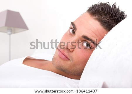 handsome sensual man lying in bed. Closeup face with seductive beautiful eyes looking at camera holding head on the pillow