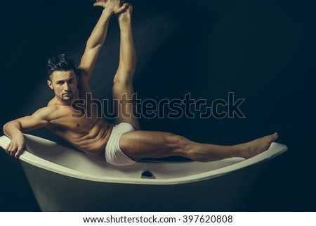 Handsome sensual sexy young stylish man in white panties bare muscular torso and beautiful body indoor sitting on bathtub in bath room with raised leg on studio background, horizontal picture - stock photo