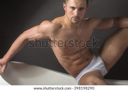 Handsome sensual sexy young stylish man in white panties bare muscular torso and beautiful body indoor sitting on bathtub in bath room on studio background, horizontal picture - stock photo