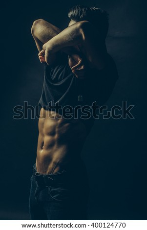 Handsome sensual sexy young stylish thoughtful man in black shirt with fashionable hairdo undressing with bare muscular torso and beautiful body indoor on studio background, vertical picture - stock photo