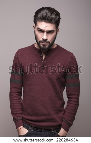 Handsome serious man wearing burgundy sweater holding his hands in pocket, looking at the camera - stock photo