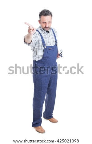 Handsome serious mechanic with wrench pointing finger in one direction or refusing to do a task isolated on white background - stock photo