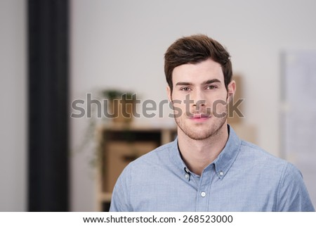 Handsome serious unshaven young man sitting looking directly at the camera at home in the living room, with copyspace - stock photo