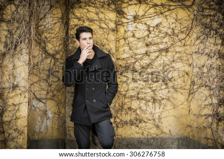 Handsome serious young man standing against plant covered wall, wearing winter clothes, smoking cigarette - stock photo