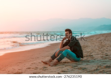 Handsome sexy and sad man sitting at beach. - stock photo