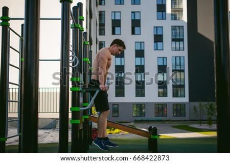 Handsome sexy male bodybuilder athlete man doing cross fit work out in athletic facilities on sunny morning outdoors. Healthy lifestyle concept.