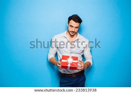 handsome sexy man on blue background with a christmas gift in hands - stock photo