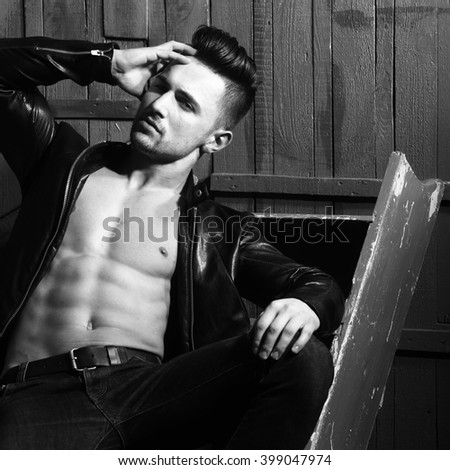 Handsome sexy muscular stylish young man in leather jacket with bare torso sitting indoor near stairs on wooden background, square picture