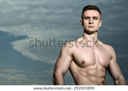Handsome sexy muscular undressed strong man bodybuilder standing on blue sky background copyspace, horizontal picture - stock photo