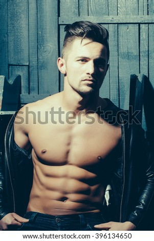 Handsome sexy sensual muscular stylish young man in leather jacket with bare torso sitting indoor near stairs on wooden background, vertical picture - stock photo