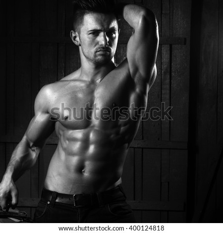 Handsome sexy sensual muscular stylish young man topless with bare torso and beautiful body standing near stairs with hard big retro suit case indoor on wooden background, square picture - stock photo