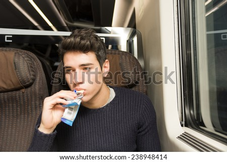 Handsome sexy young man on a train sitting in his passenger seat eating a cereal bar for a healthy snack and looking off to the side with a serious expression - stock photo