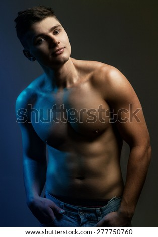 Handsome sexy young man with muscular body in jeans.