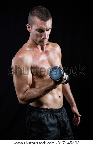 Handsome shirtless athlete working out with dumbbell against black background