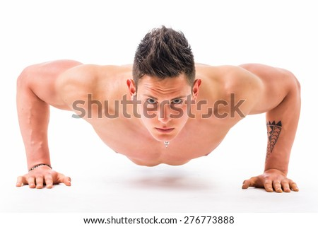 Handsome shirtless bodybuilder doing push-ups in studio shot, isolated on white. Wearing jeans