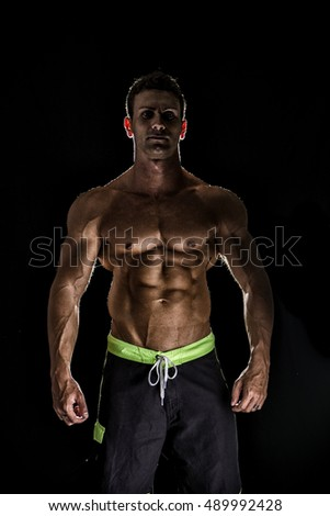 Handsome shirtless bodybuilder looking at camera isolated on black background