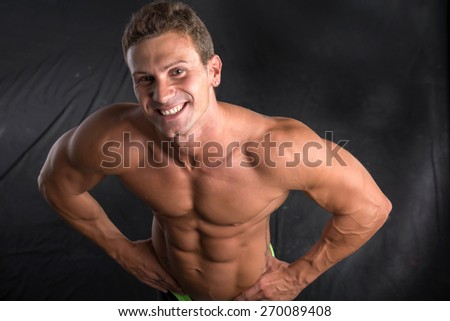 Handsome shirtless bodybuilder shot from above, standing on dark background wearing trunks
