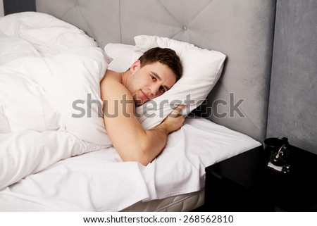 Handsome shirtless man lying in bed. - stock photo