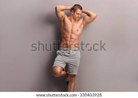 Handsome shirtless man posing against a gray wall and looking down  - stock photo