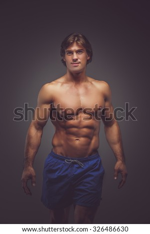 Handsome shirtless muscular man in blue shorts posing in shadow over grey background. - stock photo